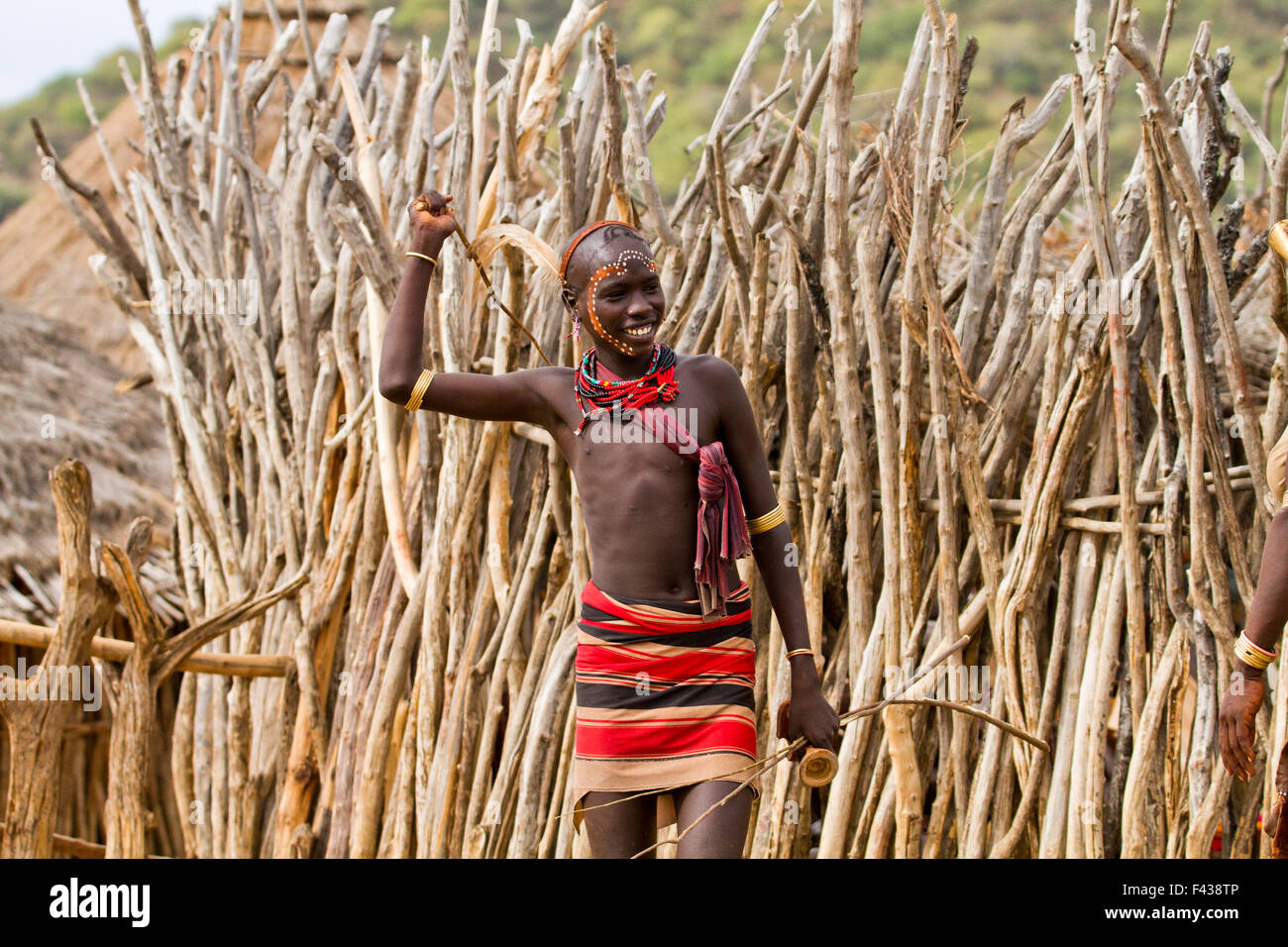 Man with reed whip ready to flog a female member at the Hamar tribe's  'Jumping of the Bull' ceremony. - Stock Image