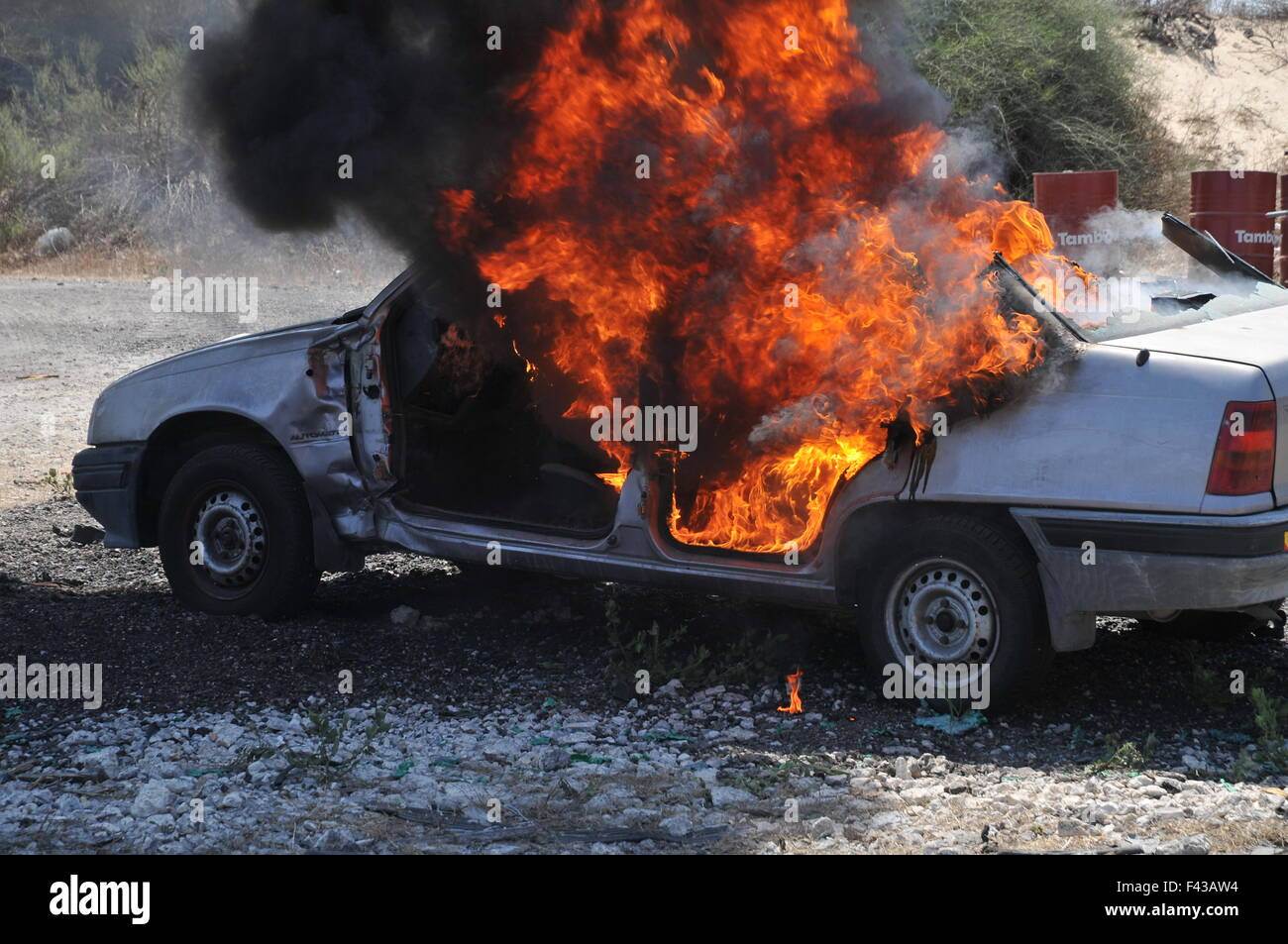 Firefighters extinguish a burning car - Stock Image