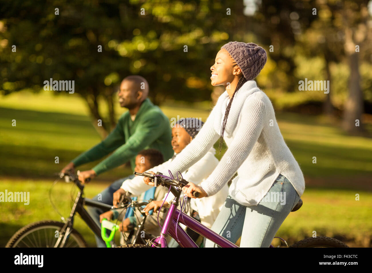 Side view of a young family doing a bike ride - Stock Image