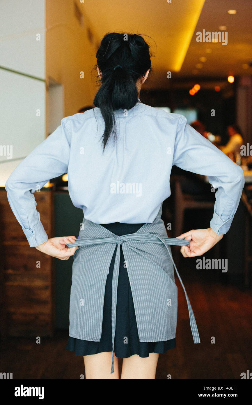 Young waitress tying her apron at a city restaurant. - Stock Image