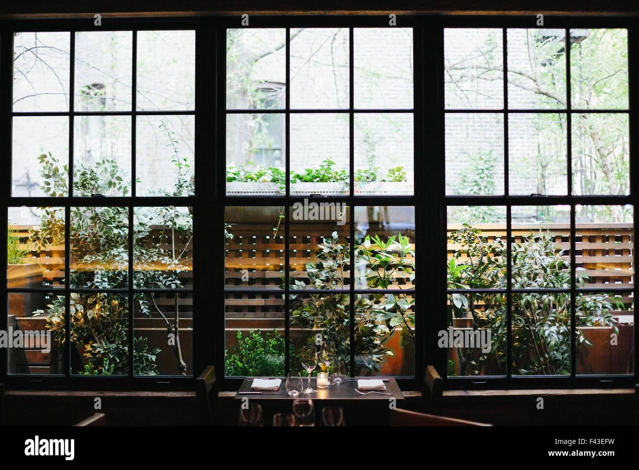 Interior view of a restaurant in Manhattan's West Village, window overlooking a garden. Stock Photo