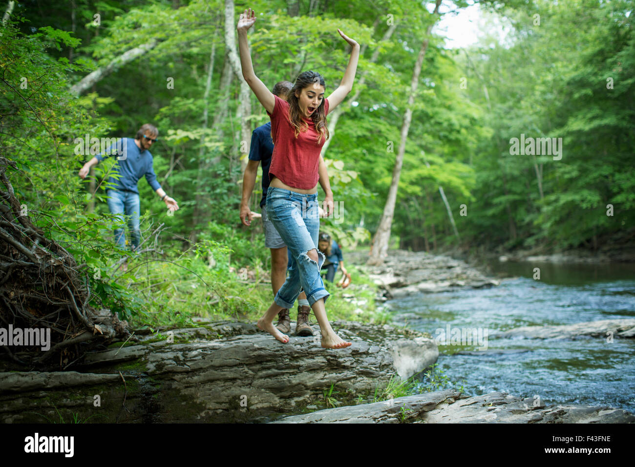 Two men and two women on the riverbank, one leaping across stepping stones. Stock Photo