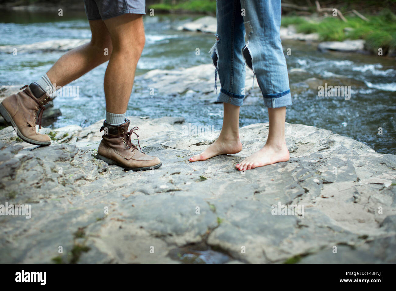Two people on the rocks by a rushing river, man and woman, lower legs and feet. - Stock Image