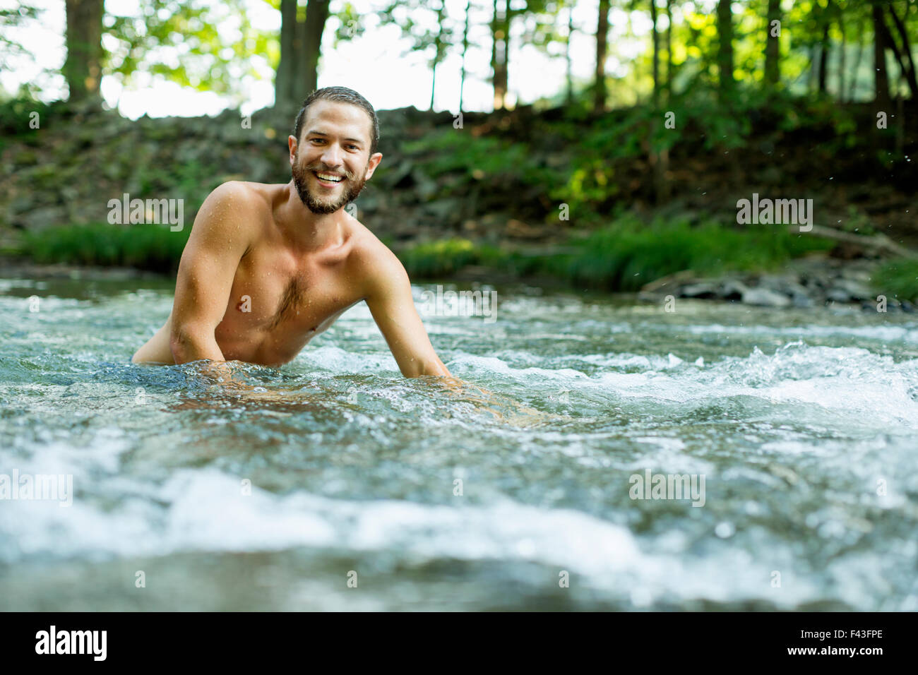A young man swimming in a fast flowing cooling stream. - Stock Image