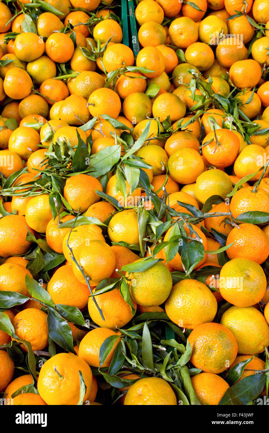 A background of fresh clementines with green leaves on a market - Stock Image