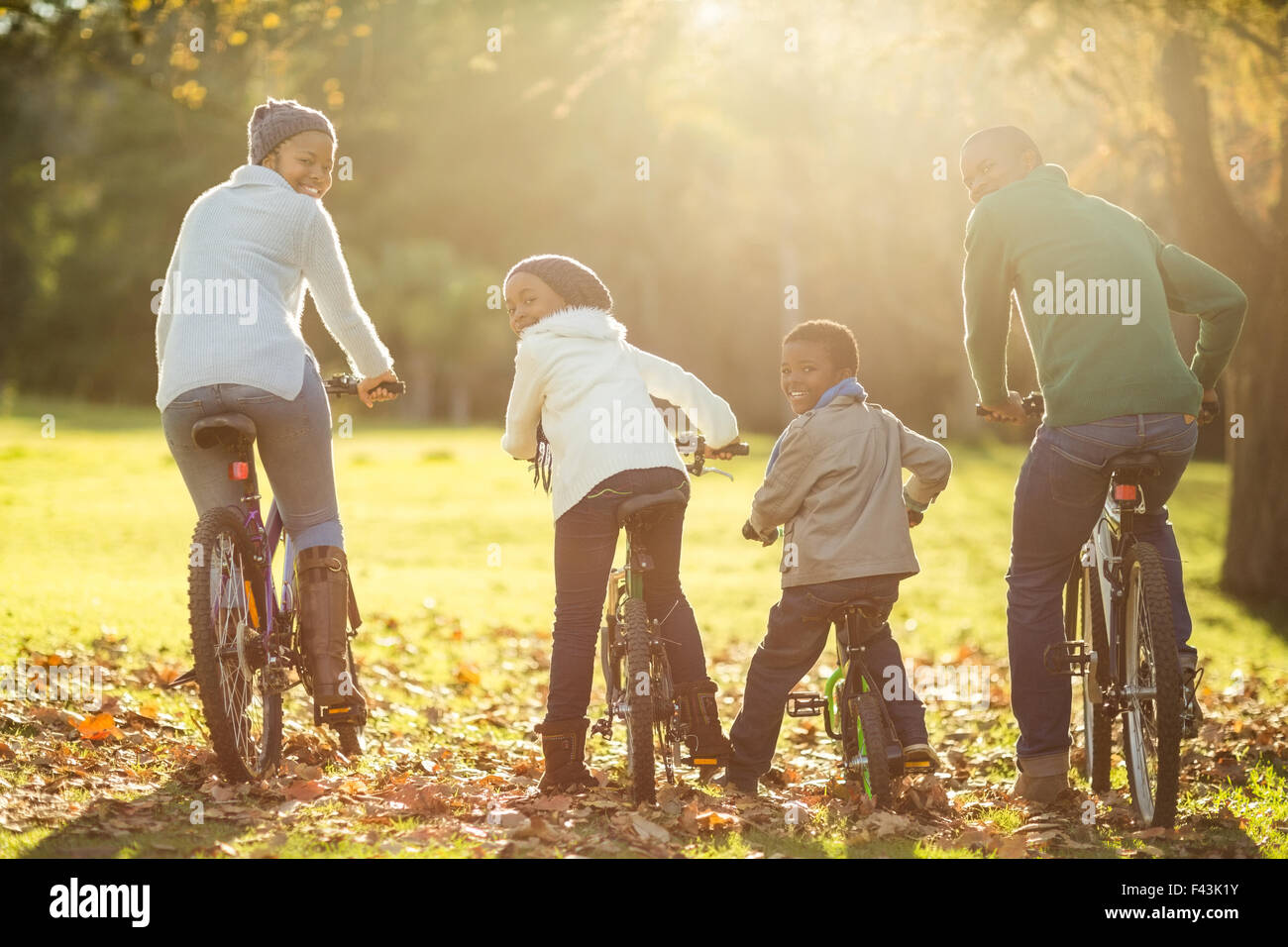 Rear view of a young family doing a bike ride - Stock Image