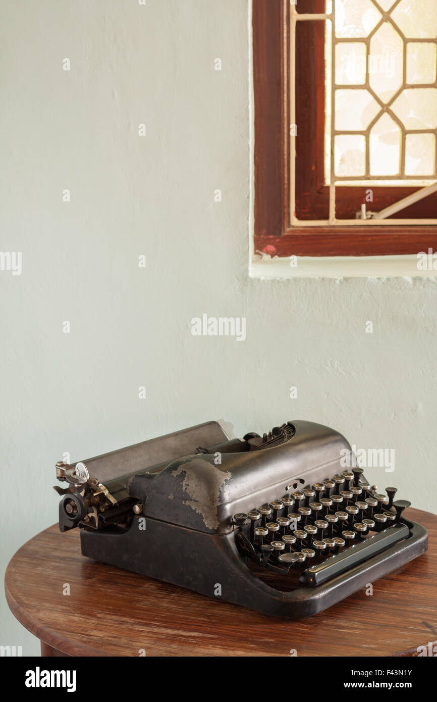 A vintage typewriter in working condition sits unused on an old desk. - Stock Image
