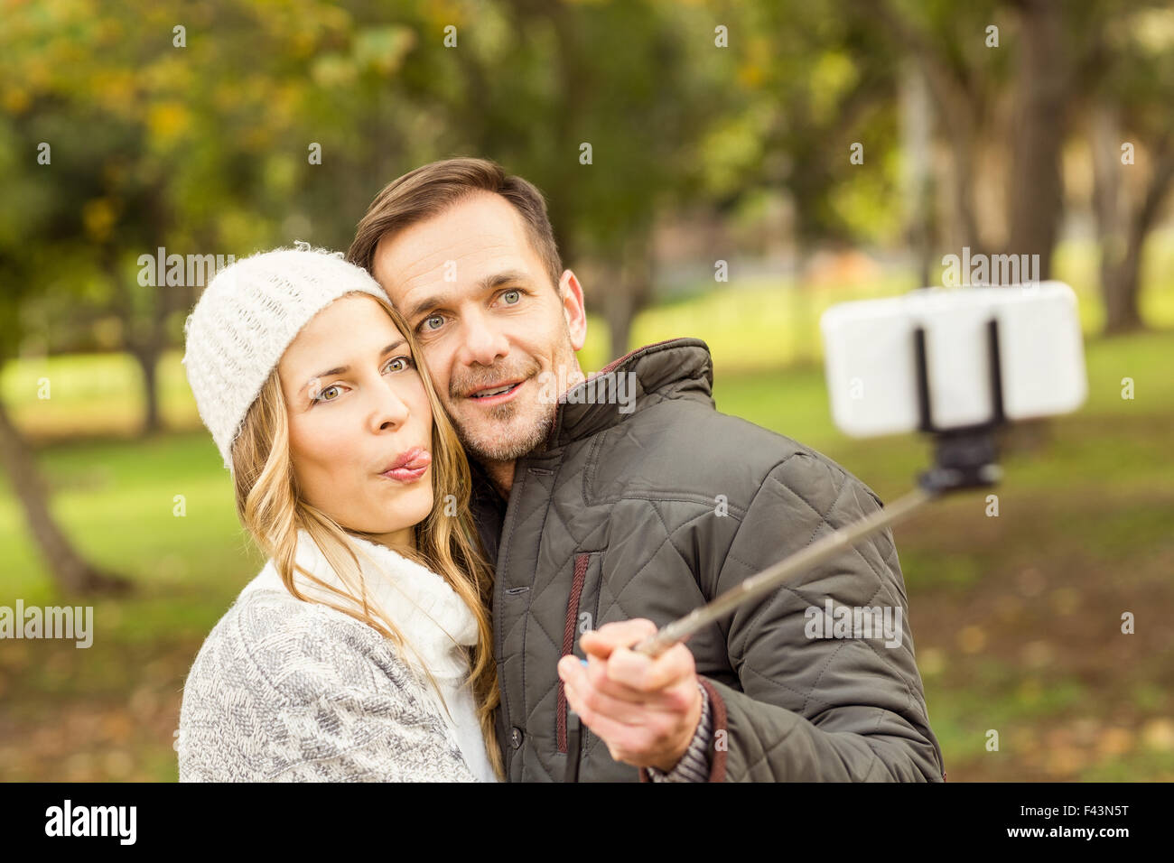 Smiling young couple taking selfies - Stock Image