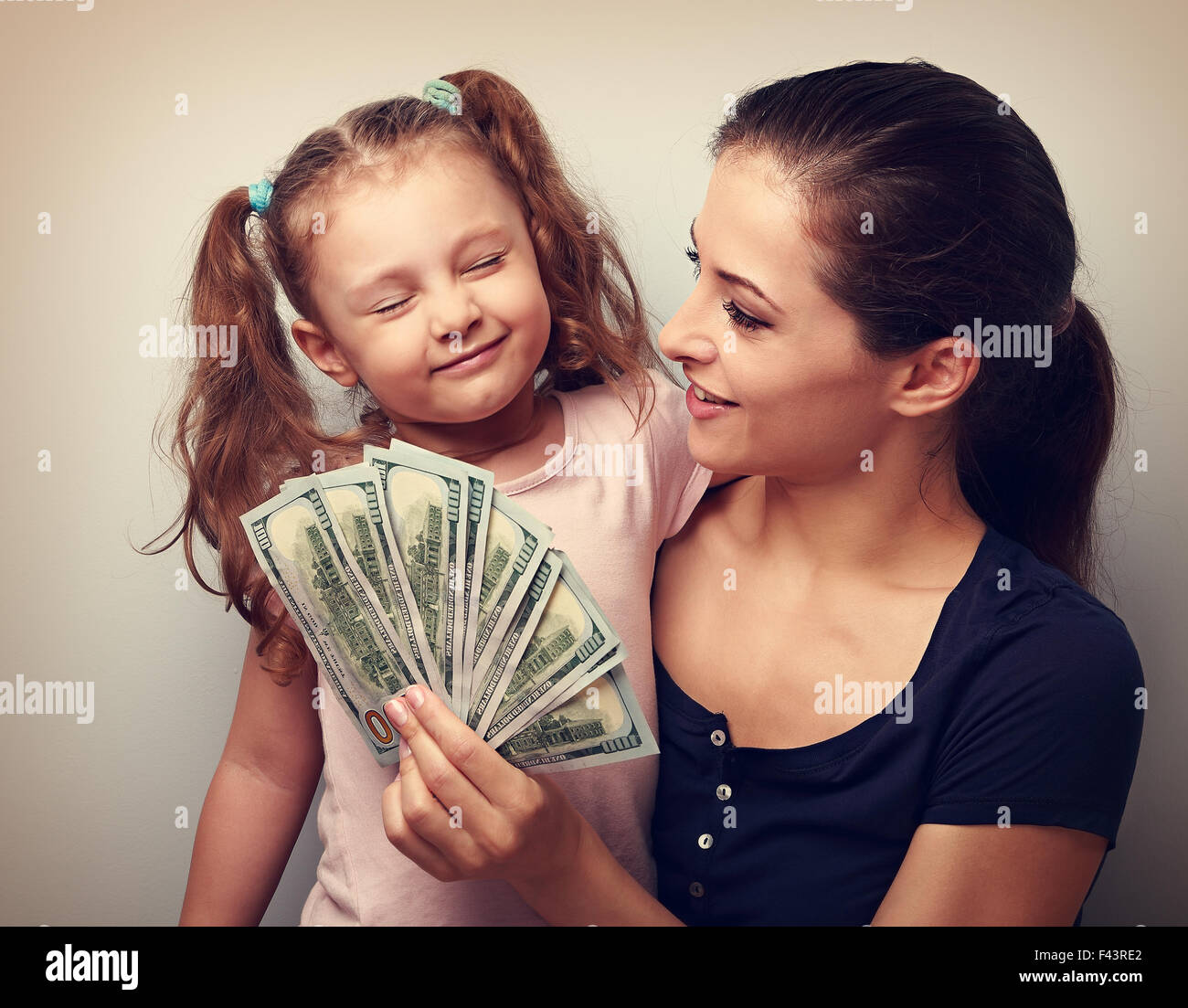 Smiling mother looking on happy daughter holding cash of dollars. Vintage closeup portrait Stock Photo