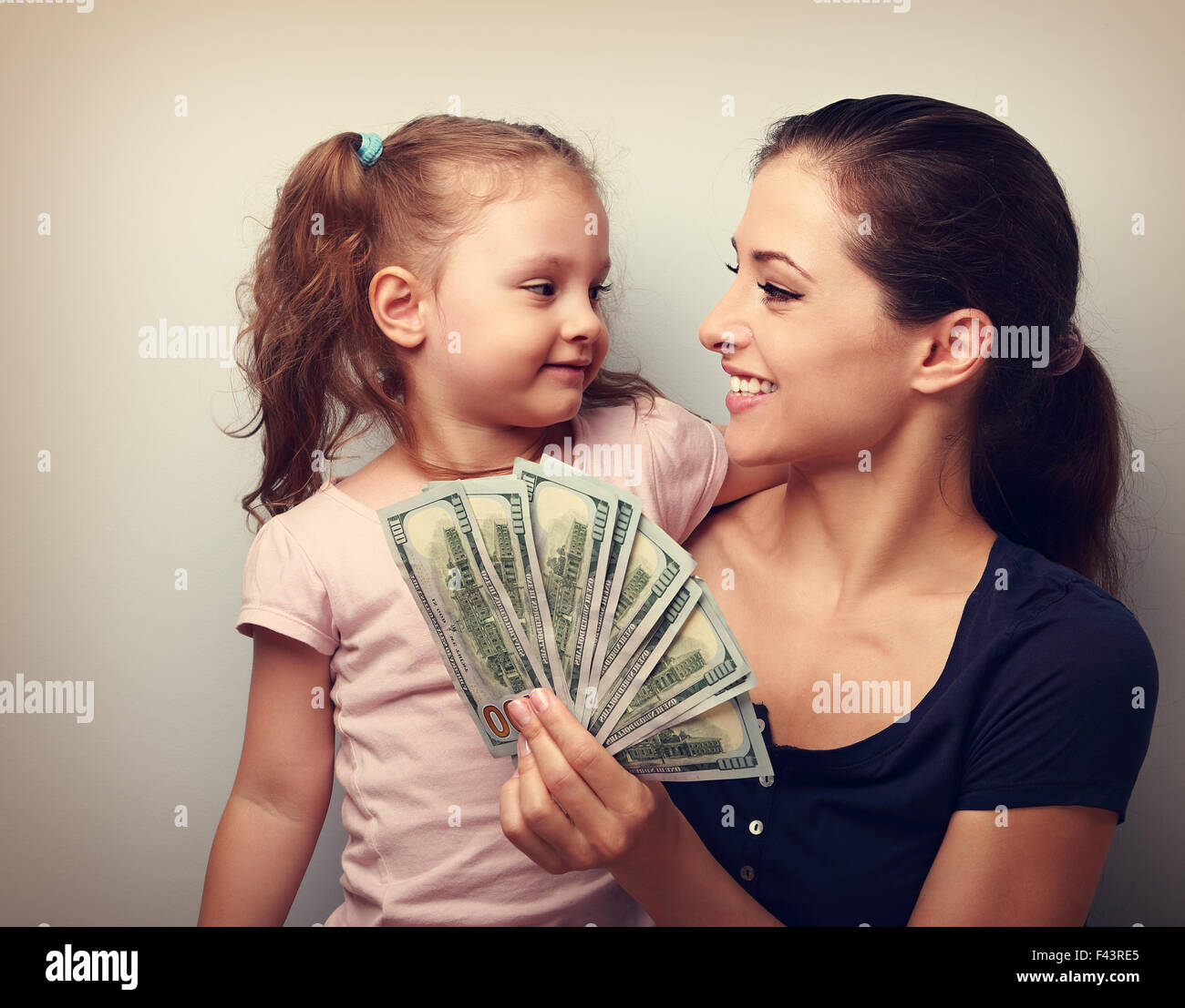Smiling winner family hugging, looking each other and holding dollars. Happiness. Vintage closeup portrait - Stock Image