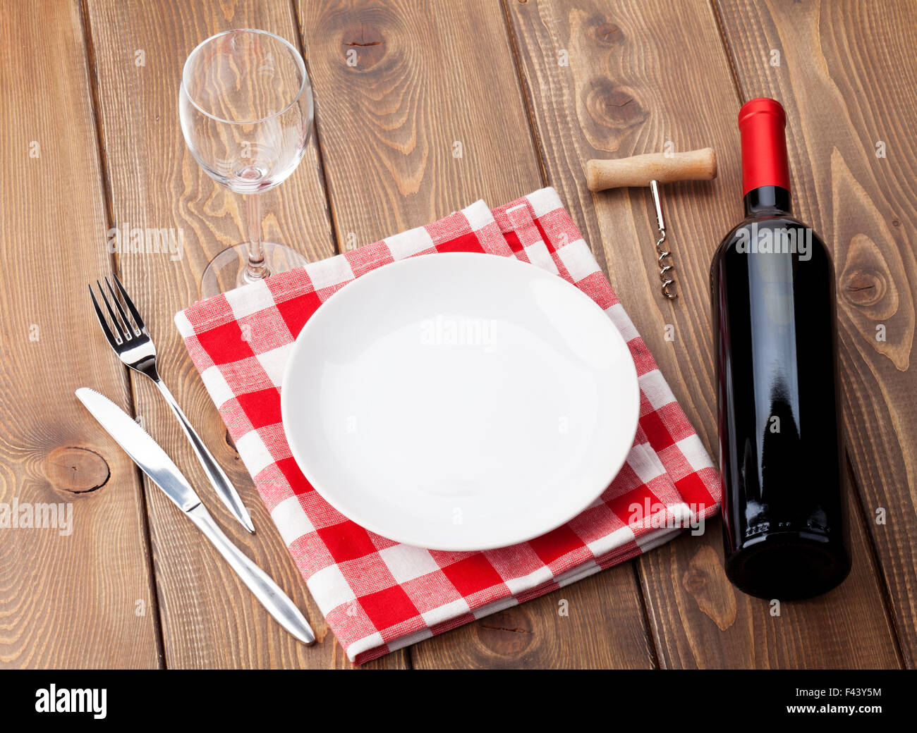 Table setting with empty plate, wine glass and red wine bottle. Top ...