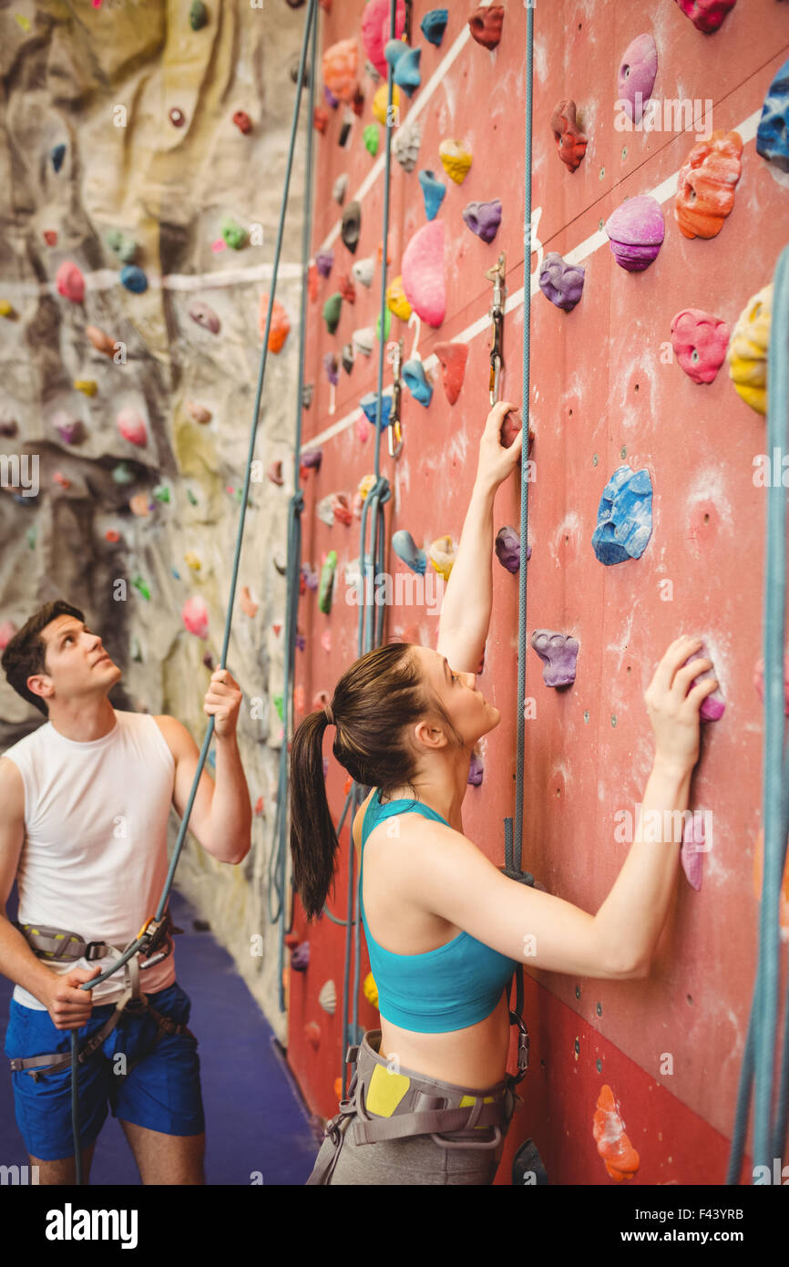 Instructor guiding woman on rock climbing wall - Stock Image