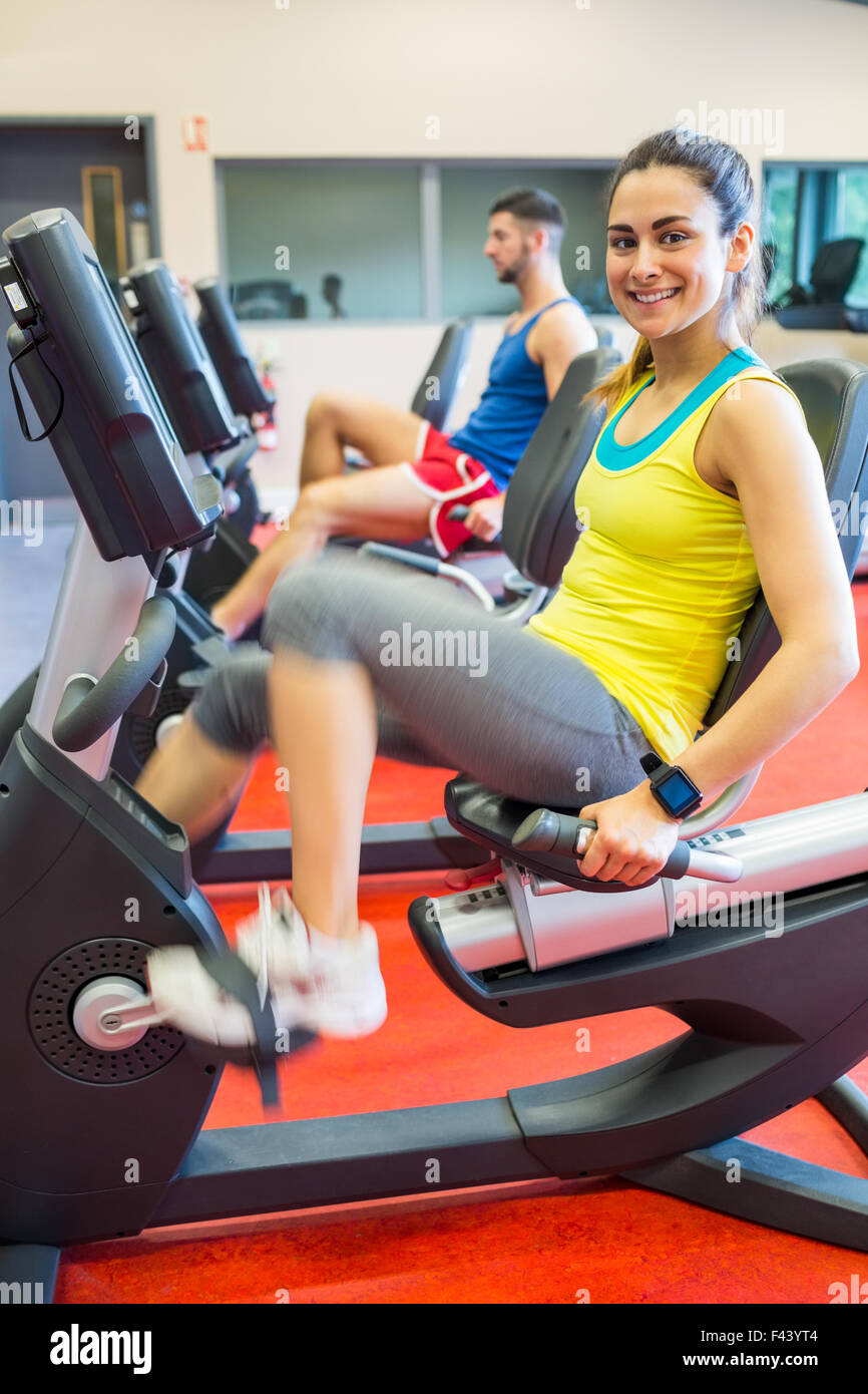 Man and woman using exercise machines - Stock Image