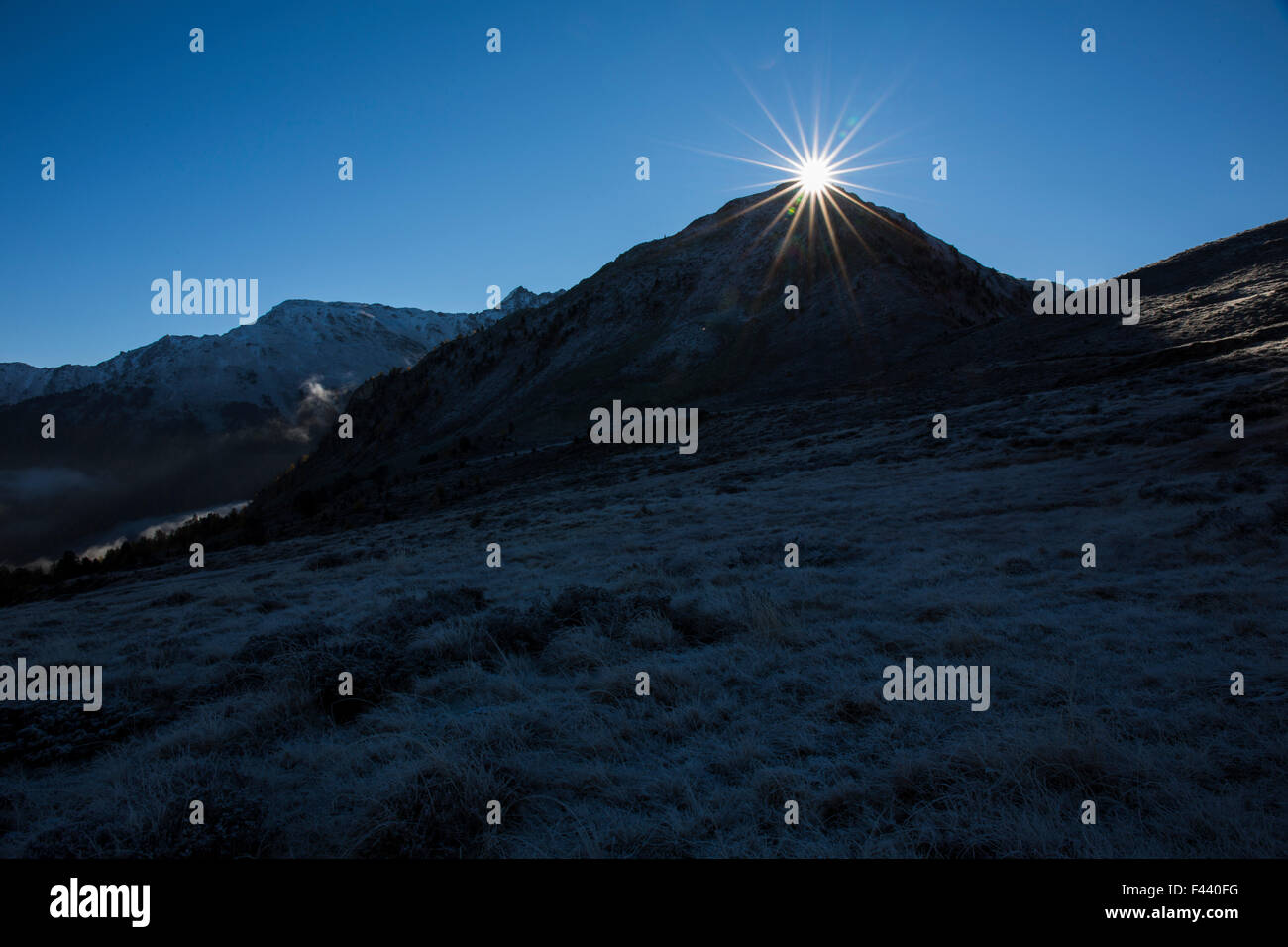 Rising Sun behind mountain - Stock Image
