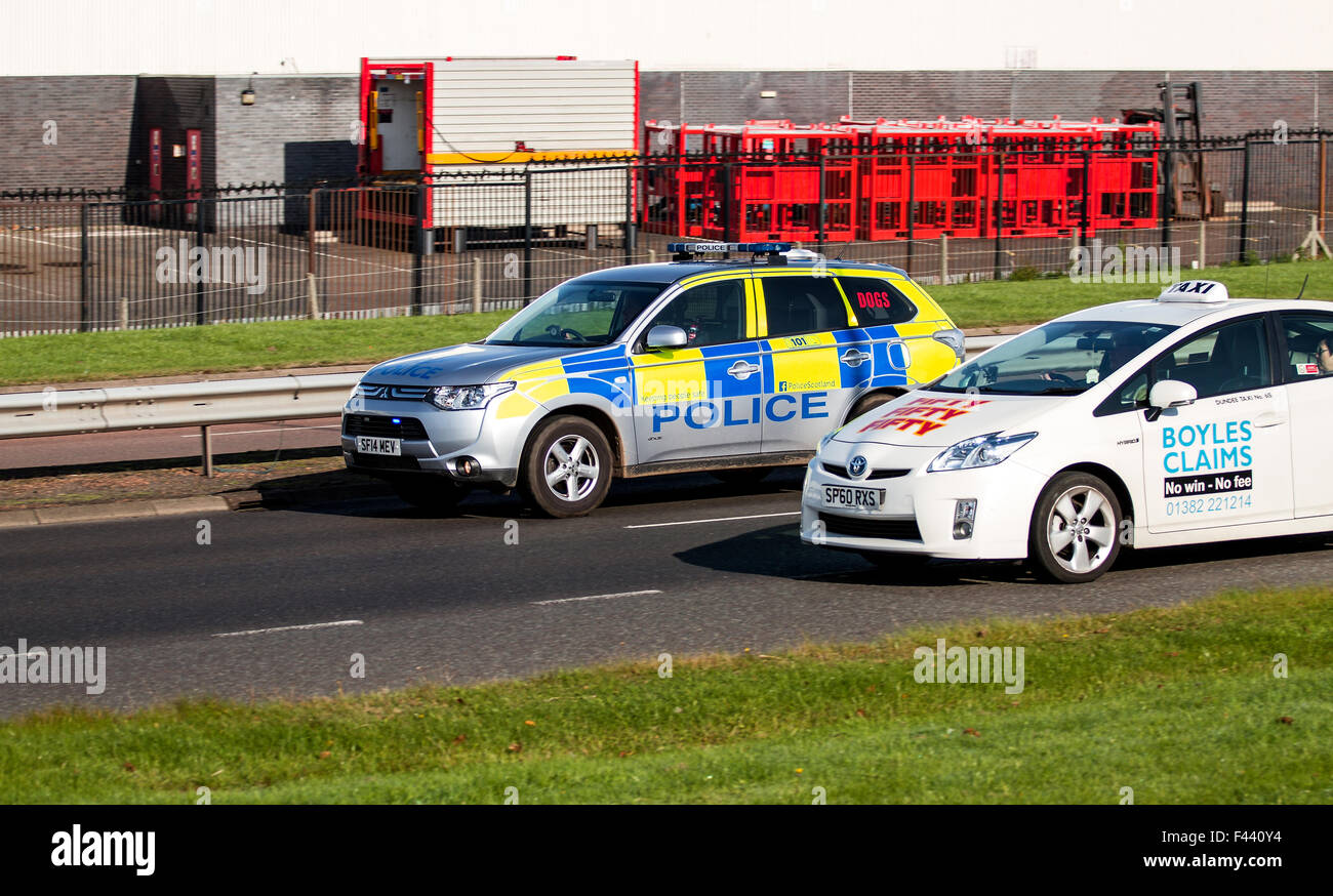 "A Taxi with Boyles ""claims"" Solicitors avert being overtaken by a Police Car on the Dual Carriageway in urban Dundee, Stock Photo"