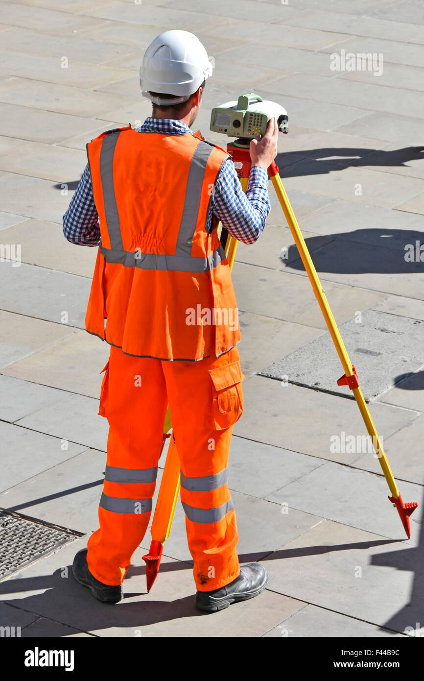 Surveyor on public pavement using tripod mounted surveying equipment wearing high vis vest & hard hat company - Stock Image