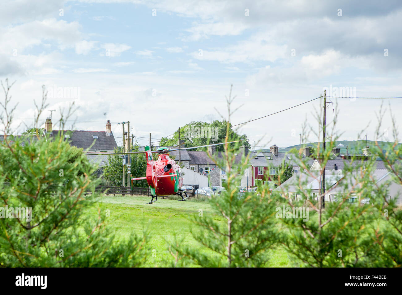 Wales air ambulance taking off after an emergency, flying within close proximity to power cables and houses - Stock Image