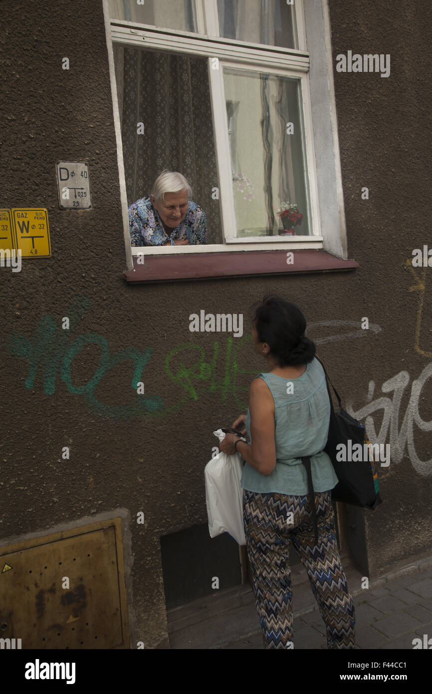Homebound old woman socializes with passersby from her apartment window in Zielona Gora, Poland. - Stock Image