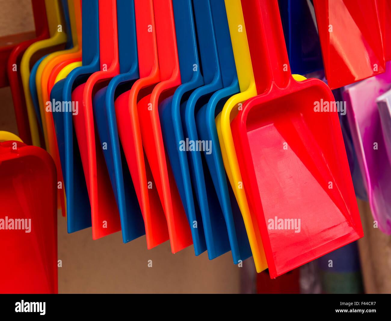 Multicoloured children's spades outside a seaside shop - Stock Image
