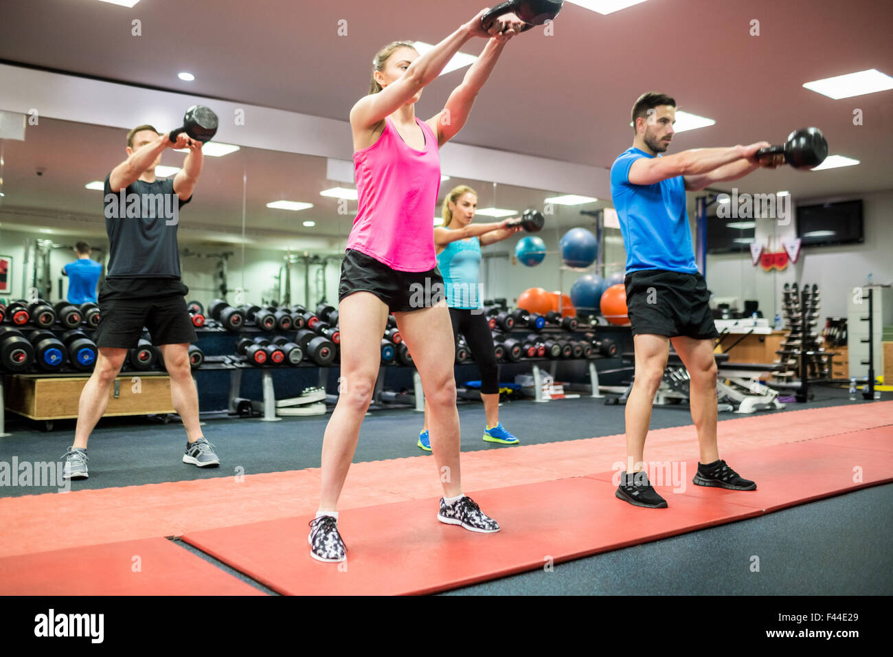 Fit people swinging kettlebell weights - Stock Image