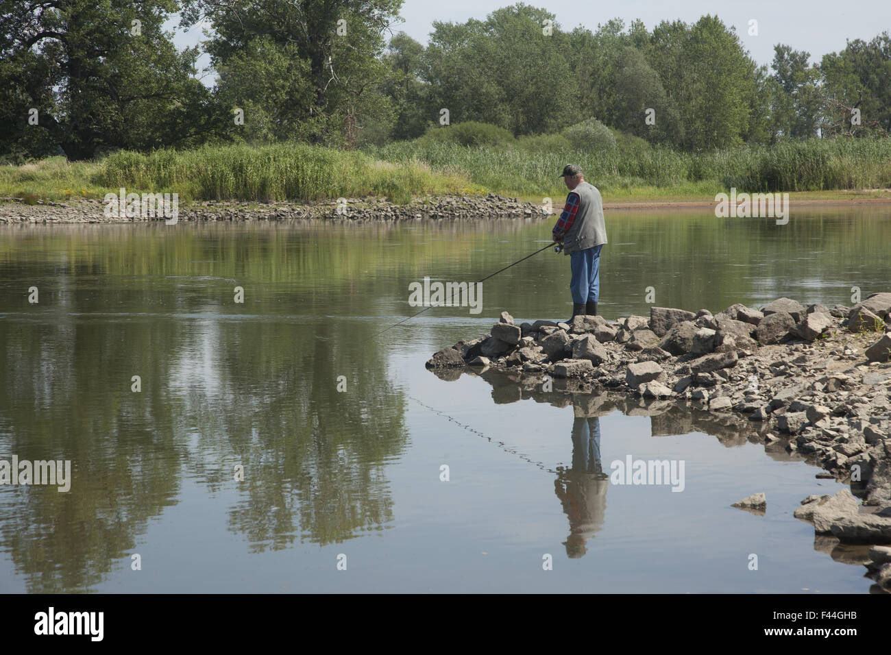 Man fishing on the River Odor the 2nd longest river in Poland. - Stock Image