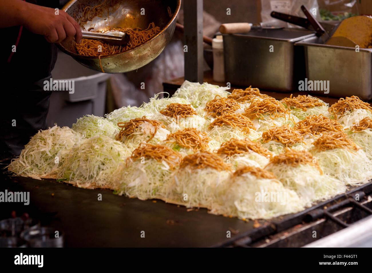 Japanese okonomi-yaki with soba noodles on top of cabbage side Stock Photo