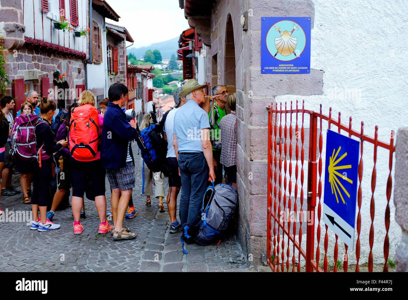 Pilgrims in front of the office of the association 'Les amis du chemin de Saint-Jacques de Compostelle' - Stock Image