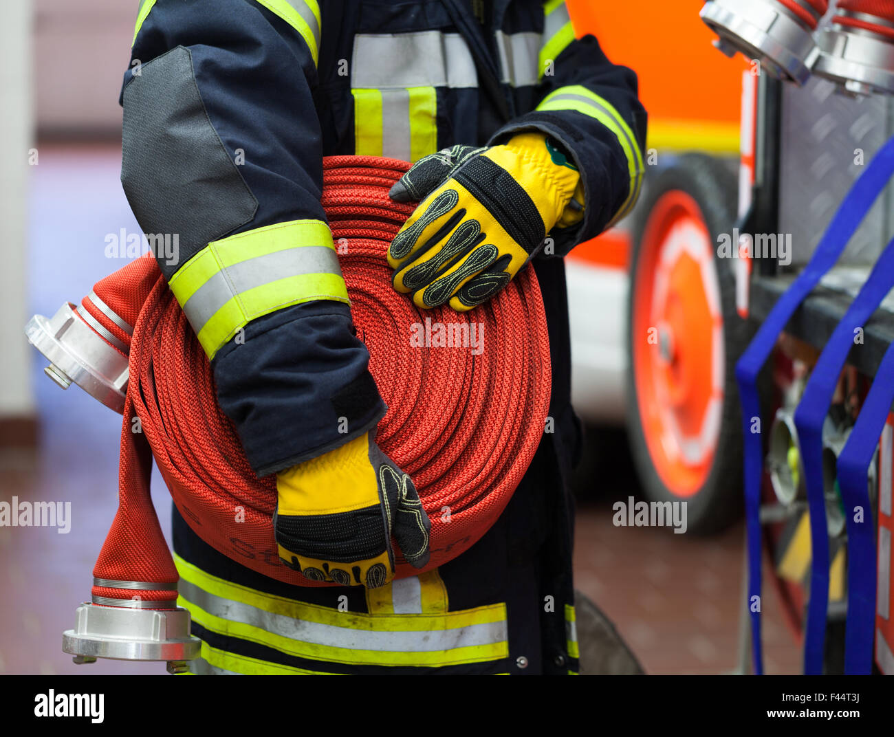 Fireman in action with water hose - Stock Image