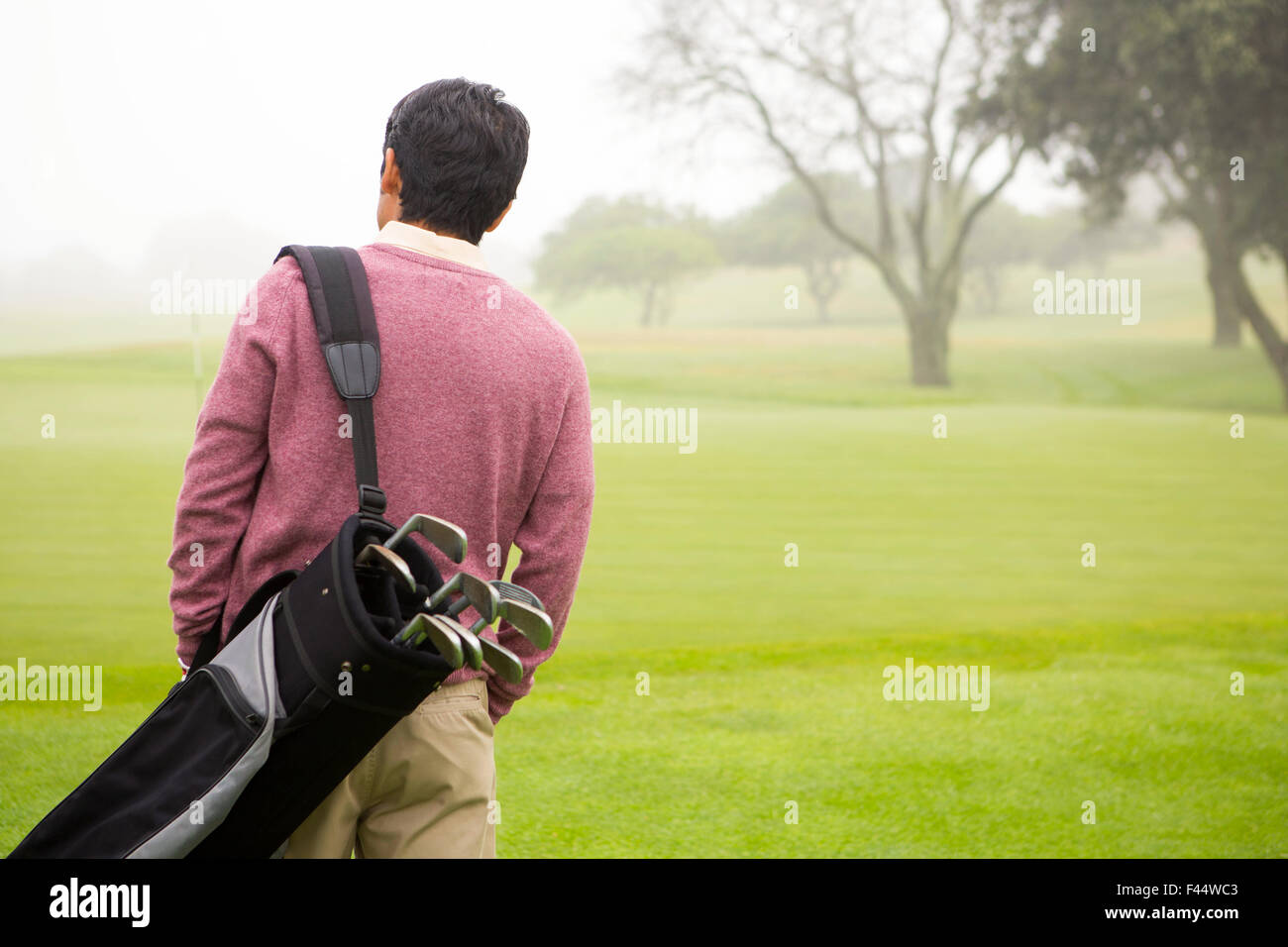 Golfer walking and holding his golf bags - Stock Image