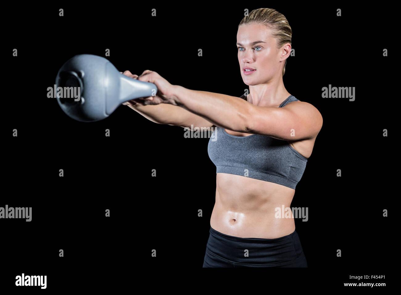 Muscular woman swinging heavy kettlebell Stock Photo