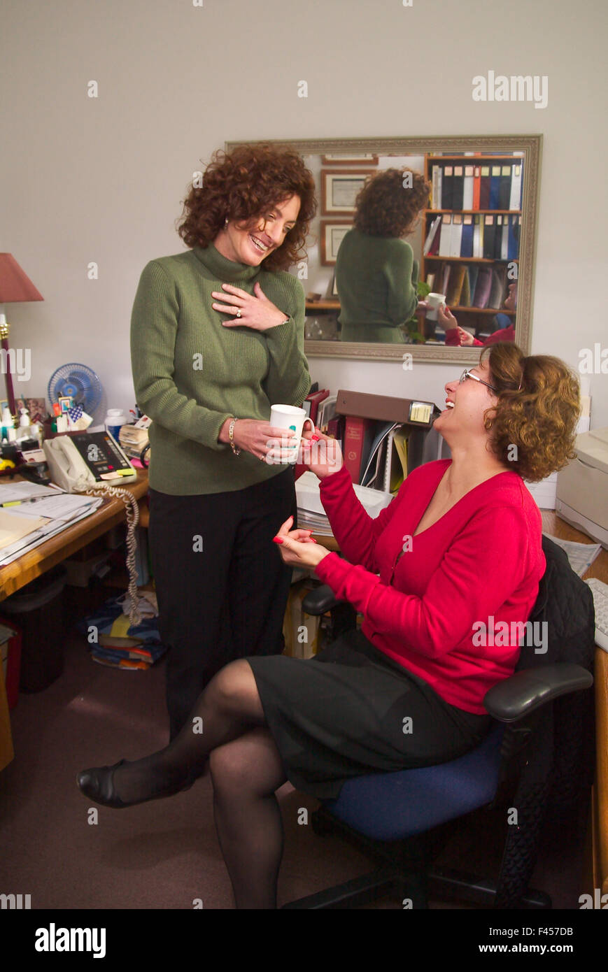 Two community college faculty members share a laugh in a Mission Viejo, CA, campus office. - Stock Image