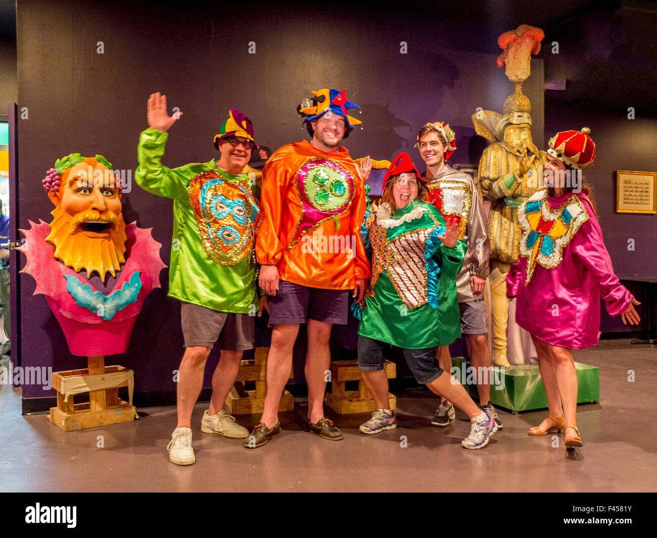 Tourists in fanciful garish costumes pose in New Orleans, LA, at Mardi Gras World, where parade floats are built. - Stock Image