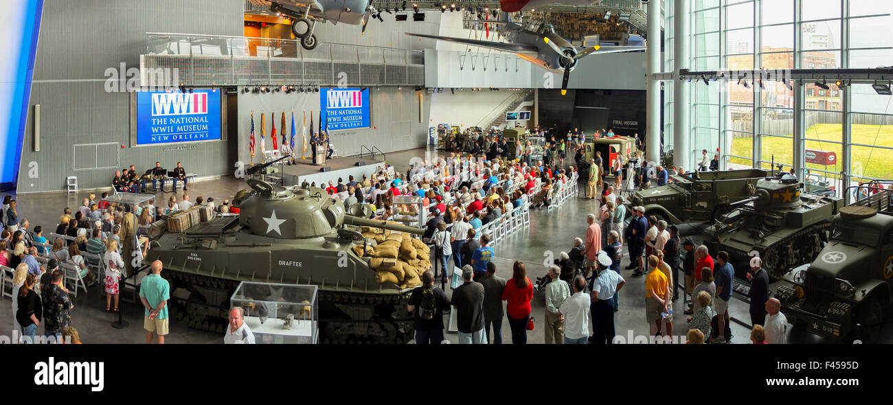 Surrounded by historical weapons, a crowd gathers for a Memorial Day observance at the Nation World War II Museum - Stock Image