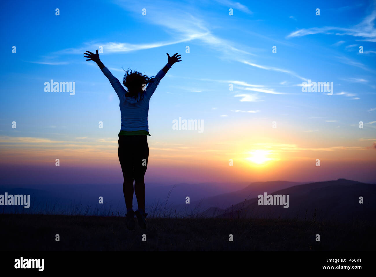 Silhouette of jumping young woman - Stock Image