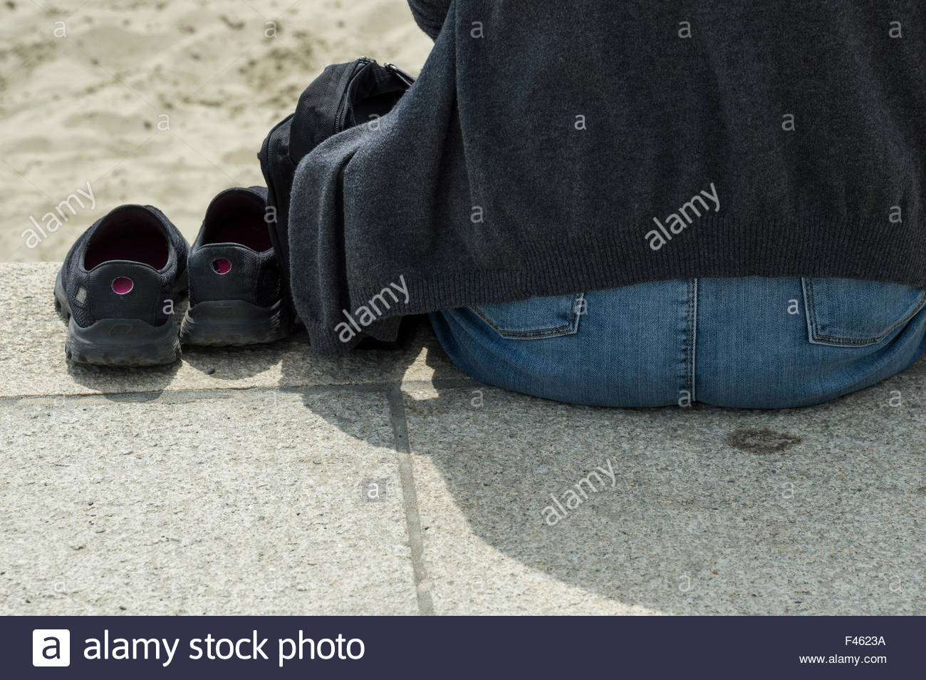 Woman sitting by the beach with her shoes next to her - Stock Image