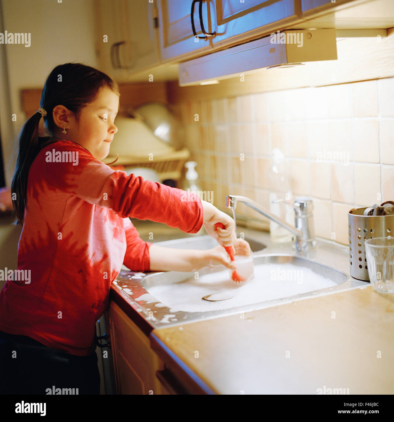 A girl washing up the dishes, Sweden. - Stock Image