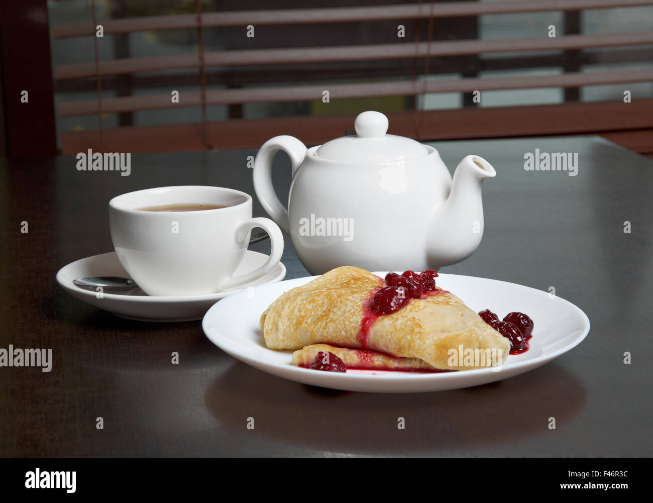 teapot, cup of tea and pancakes on plate with sweet cherry confiture - Stock Image