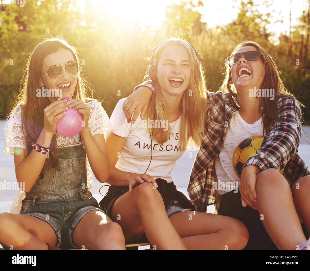 Group of girls laughing while sitting outside enjoying the summer - Stock Image