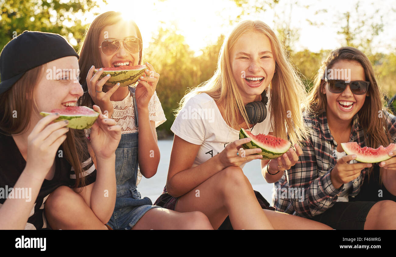 Group of friends having fun eating water melon outside - Stock Image