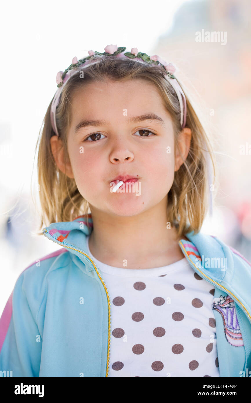 A girl eating a lollipop. - Stock Image