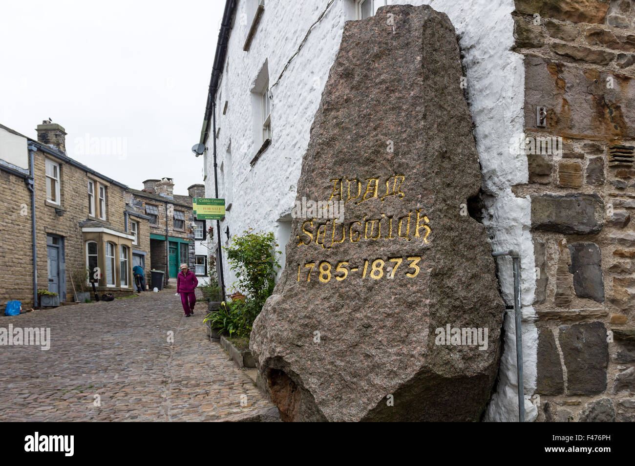 Granite Memorial to Geologist Adam Sedgwick with House For Sale Sign Behind in the Village of Dent, Dentdale, Cumbria - Stock Image