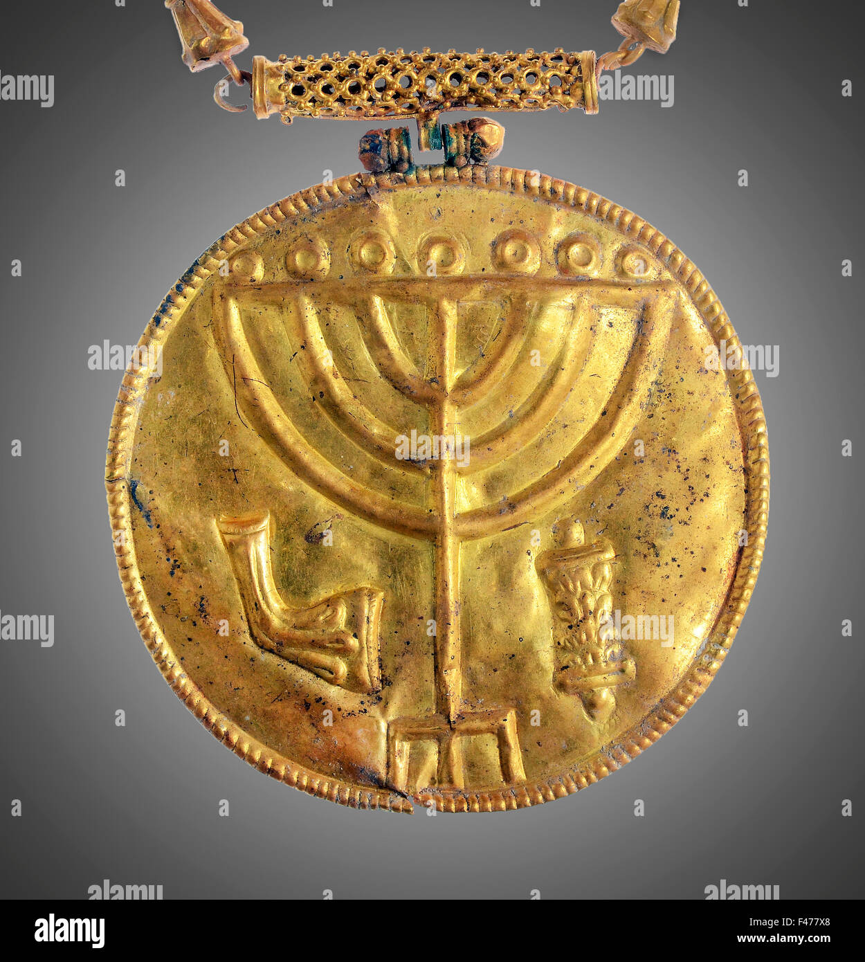 5812. Golden medallion decorated with a seven branched menorah (candelabra), a ram's horn and a Torah scroll. The - Stock Image