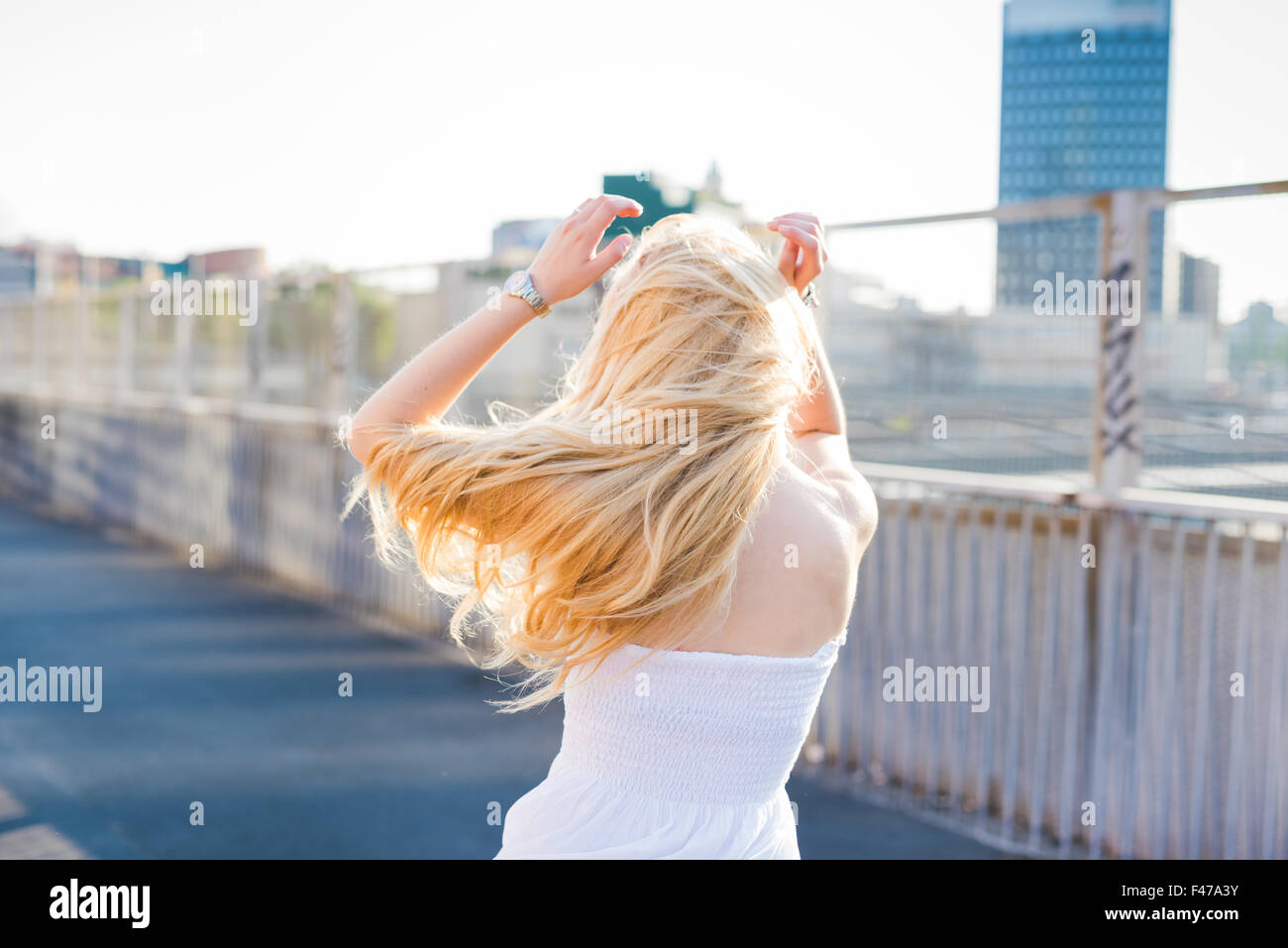young handsome caucasian long blonde straight hair woman dancing in the city, view from back, feeling free in the - Stock Image