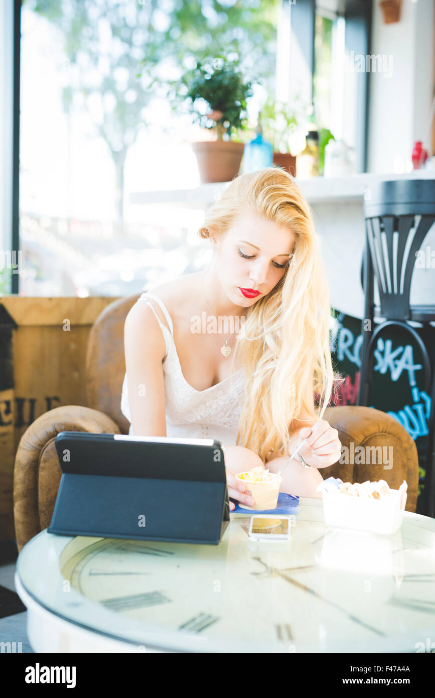 young handsome caucasian long blonde straight hair woman sitting on a bar, using a tablet, eating an ice cream, - Stock Image