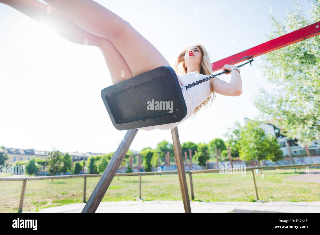 young handsome caucasian long blonde straight hair woman having fun on a seesaw in a playground looking upward  - Stock Image