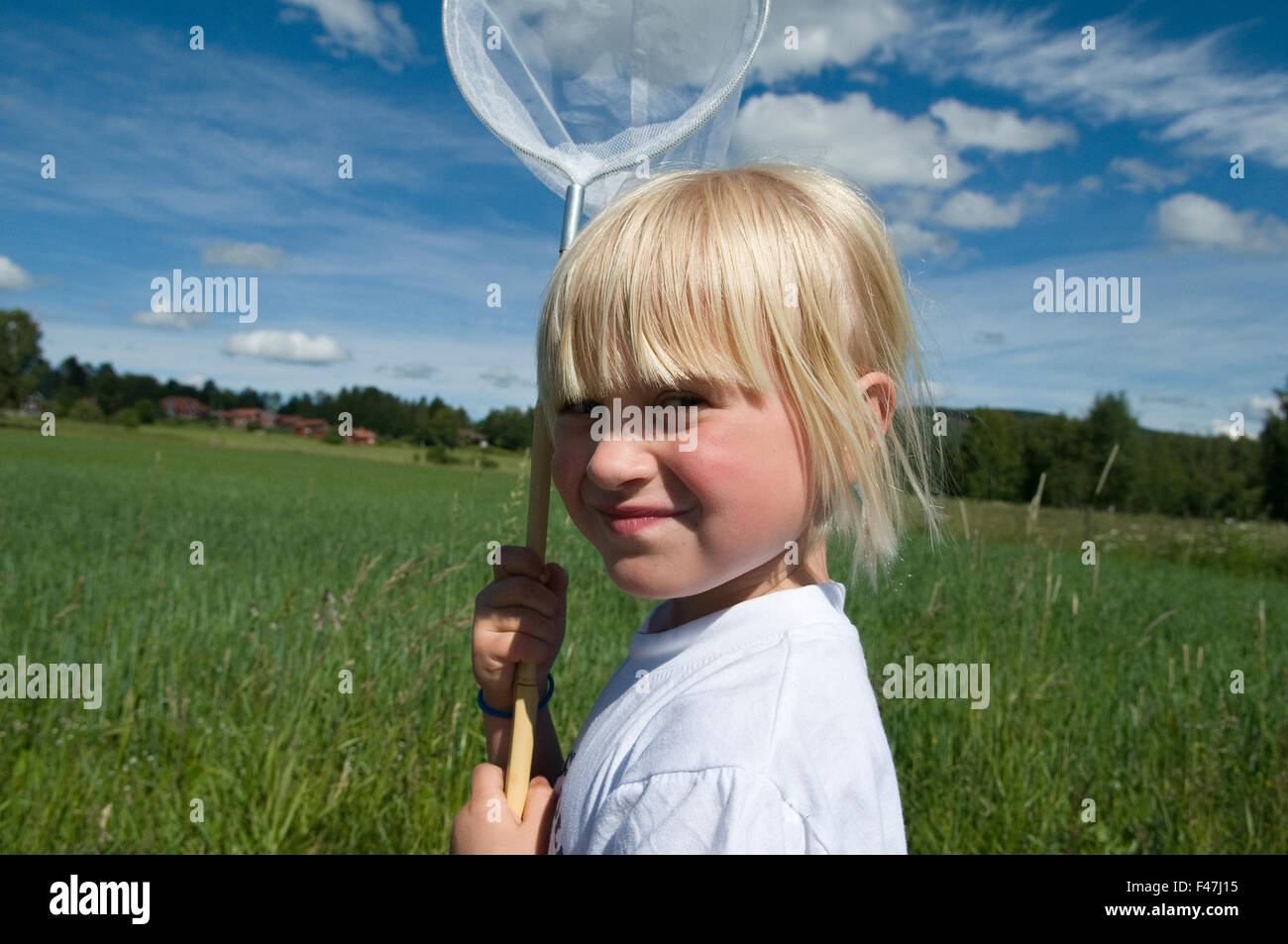 A girl holding a butterfly-net, Sweden. - Stock Image