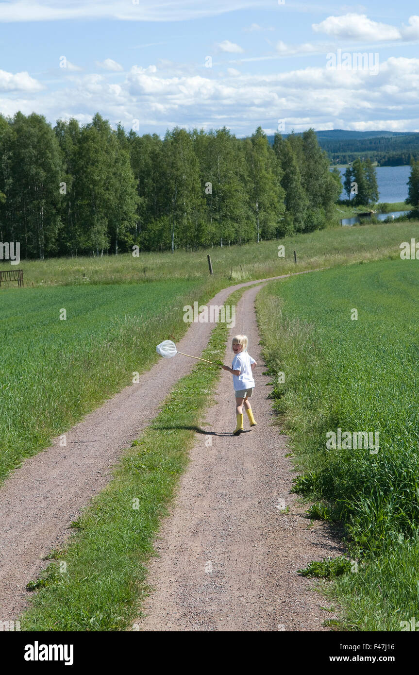 A girl running on a gravelled road carrying a butterfly-net, Dalarna, Sweden. - Stock Image
