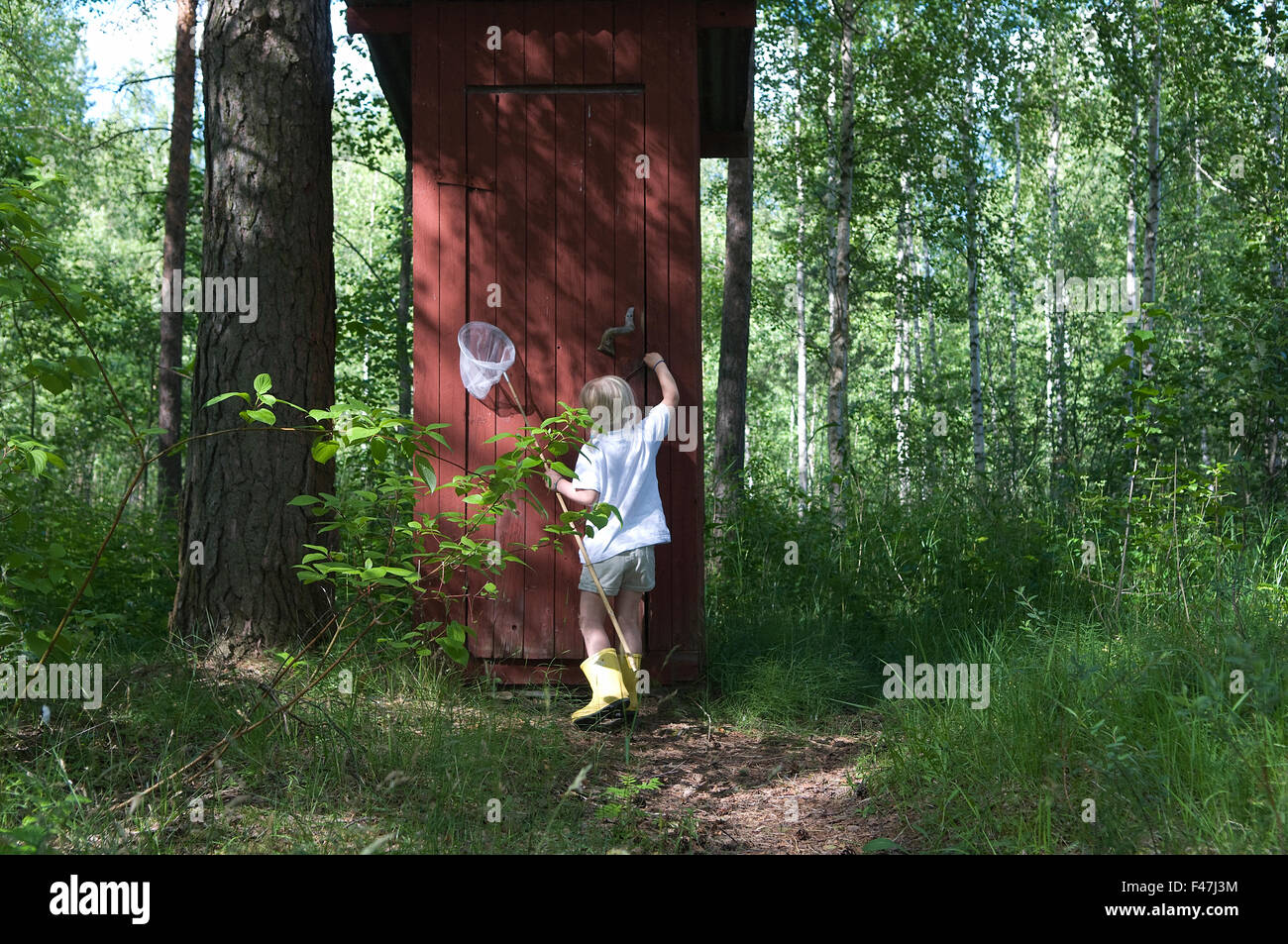 Girl running to an outhouse, Sweden. - Stock Image