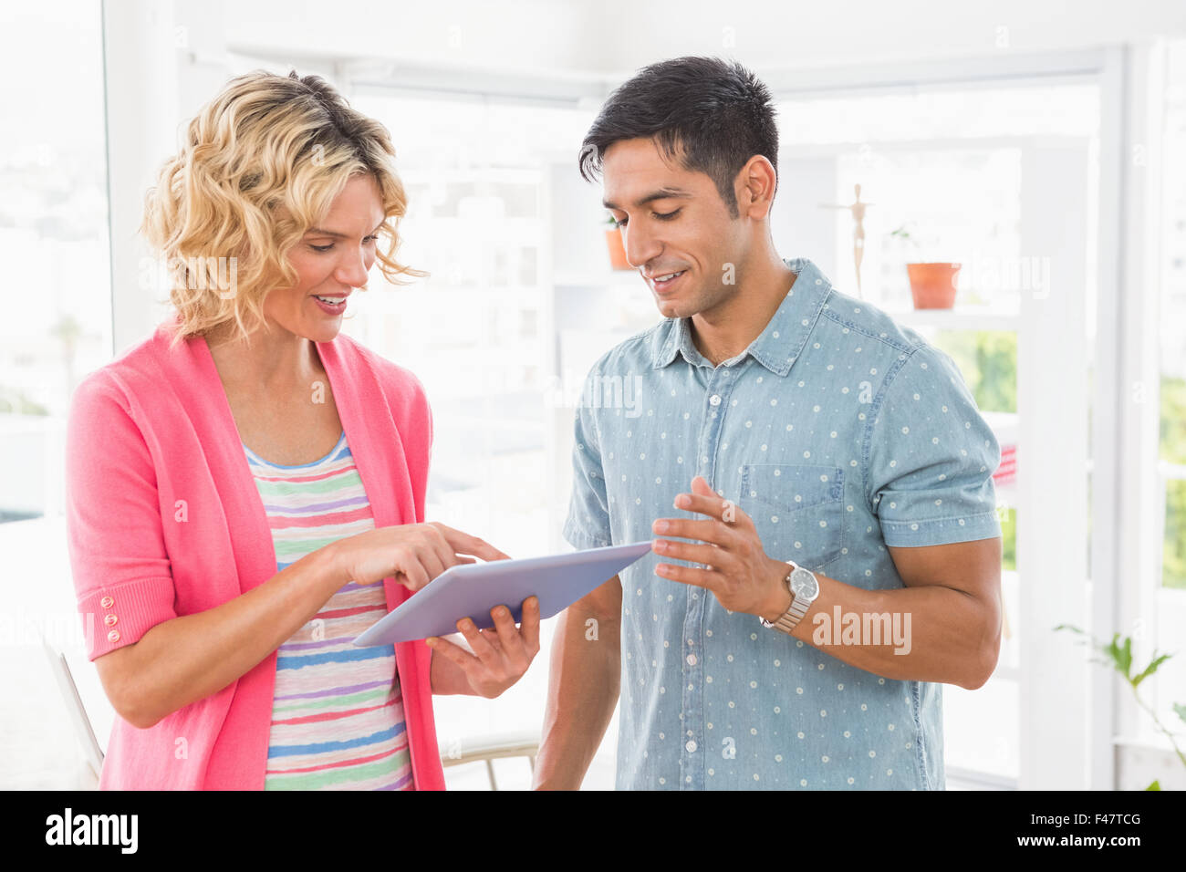 Colleagues standing and using tablet computer together Stock Photo