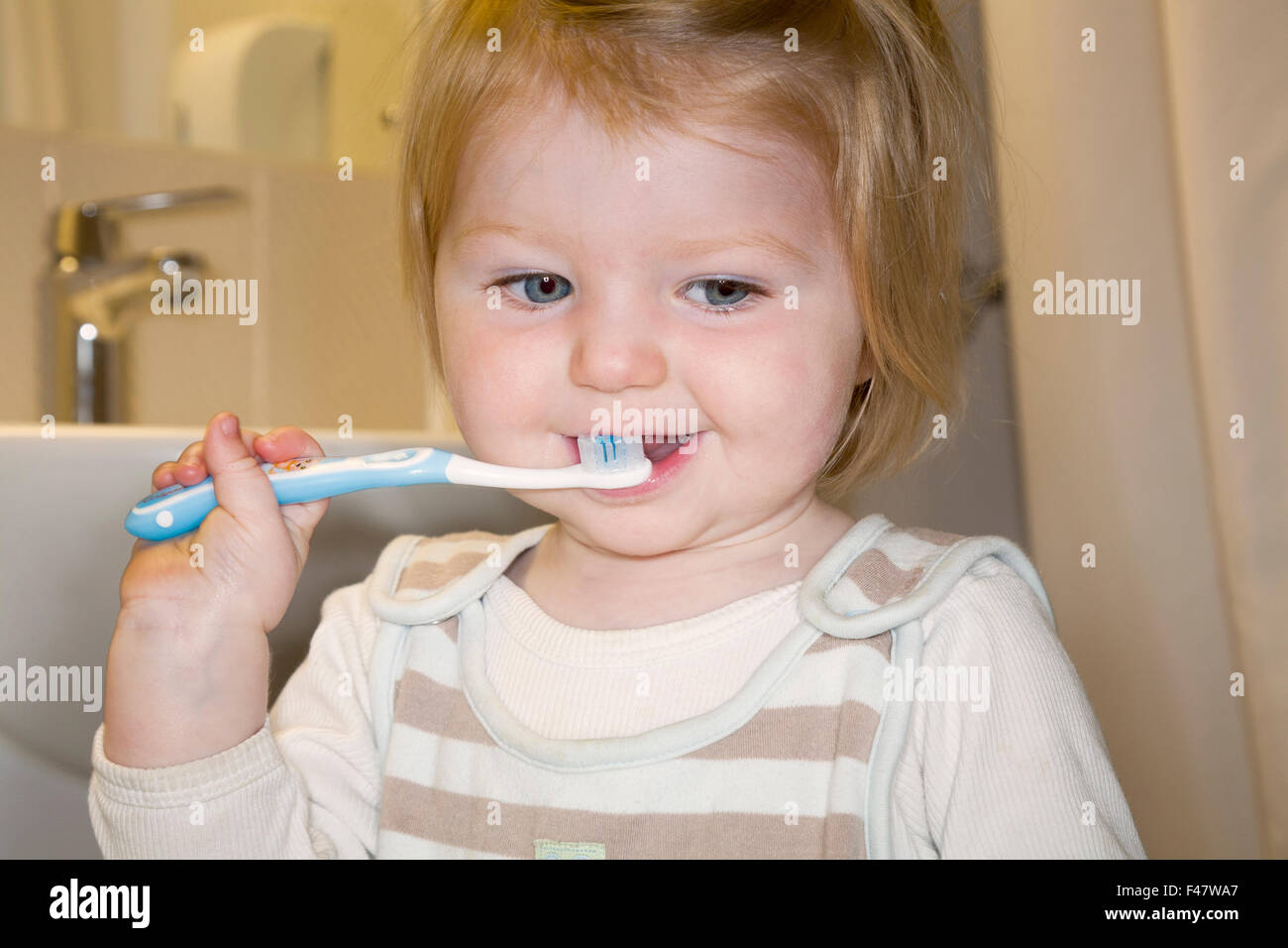 Child / baby practising brushing her teeth with a toothbrush / tooth brush for the first time. Stock Photo